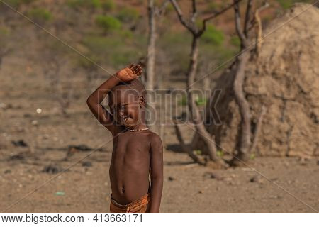 Khorixas. Namibia, January 13. 2020: Himba Tribe Boy Stay And Looking To The Camera At The Himba Vil