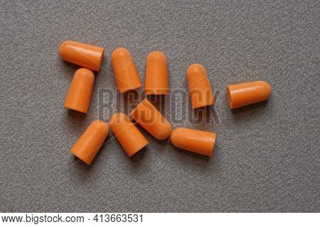 Heap Of Red Plastic Earplugs On A Gray Table