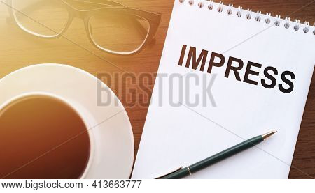Impress - Text On Paper With Cup Of Coffee And Glasses On Wooden Background In Sinlight.