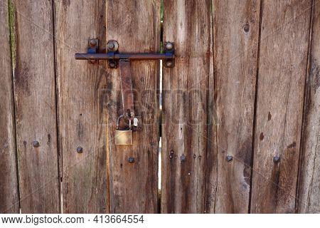 Old Metal Bolt With A Lock On A Wooden Door. Door Latch