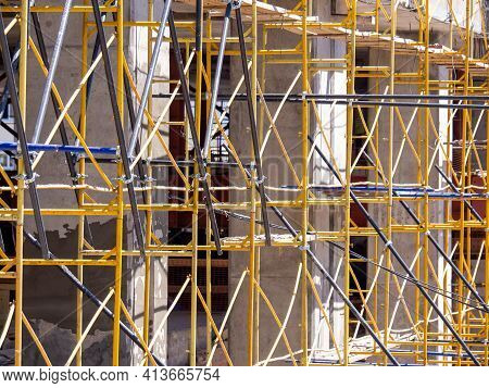 Scaffolding At A Construction Site Near A Concrete Building. Construction Worker Safety. Metal Struc
