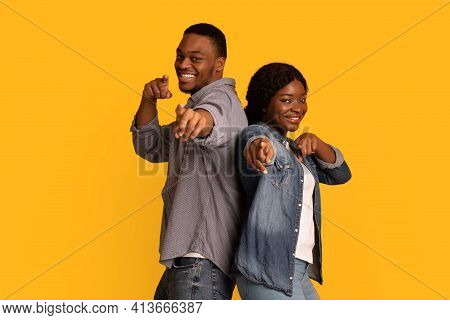 Gotcha. Joyful African Man And Woman Pointing At Camera With Fingers