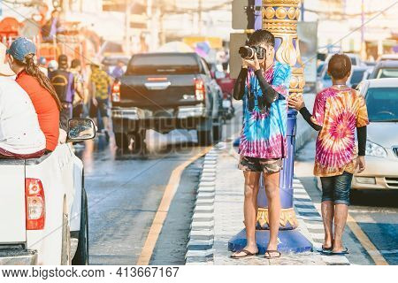 A Young Photographer In Wet Clothes Use Dslr Camera To Take Pictures Of Songkran Water Splashing Fes