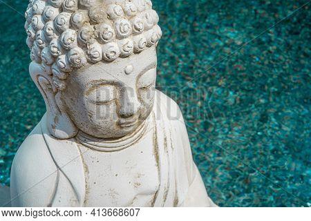 White Buddha Statue On Azure Water Background. Founder Of Buddhism. Close Up.
