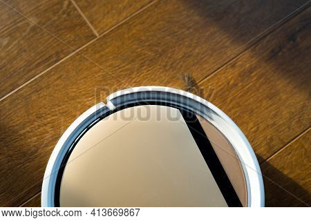 Light Robot Vacuum Cleaner Collects Dust On A Wooden Laminate In The Sun Glare. Close Up Photo