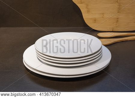 Empty White Plates, Wooden Cutting Board And Wooden Spoons On A Dark Table Background. Clean Modern