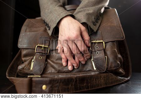 Teachers Hands Are On An Old Leather Briefcase With Metal Buckles On The Table.