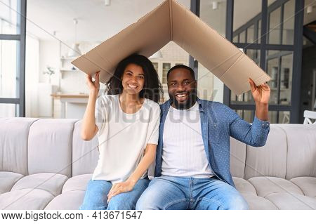 Hilarious And Excited African-american Young Couple Sits On The Couch At New Home, Holds Cardboard R