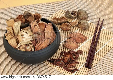 Traditional dried chnese herbs used in herbal medicine in a bowl, and loose with chopsticks on bamboo. Alternative healthcare concept.