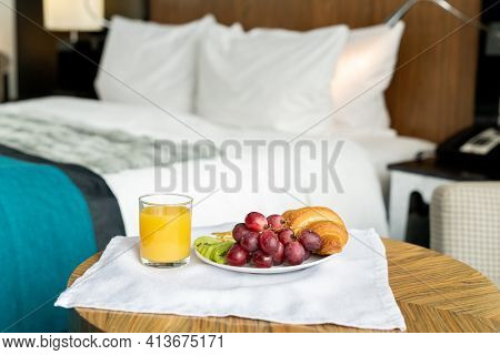 Tray with breakfast standing on small wooden table in front of camera against bed inside one of rooms of contemporary luxurious hotel