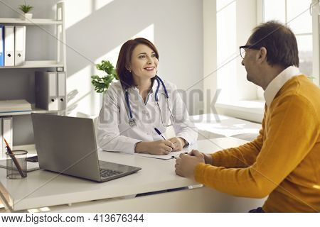 Friendly Woman Doctor Listening Patient Complaints At Medical Consultation