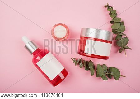 Flat Lay With Natural Organic Cosmetics: Serum, Cream On Pink Background With Green Leaves. Skincare