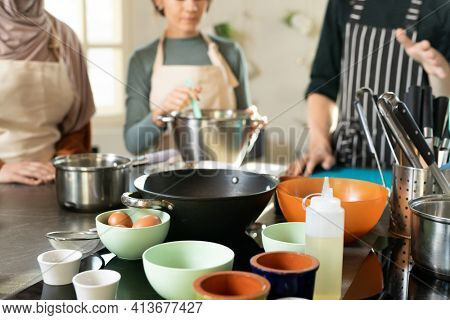 Group of bowls with ingredients on kitchen table on background of cooking coach in striped apron explaining learners how to cook