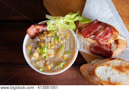 Corn Chowder Soup With Bacon. Brown Wooden Background. Close-up View