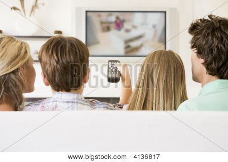 Families In Living Room With Remote Control And Flat Screen Television
