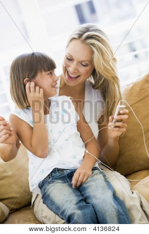 Woman And Young Girl In Living Room With Mp3 Player Smiling