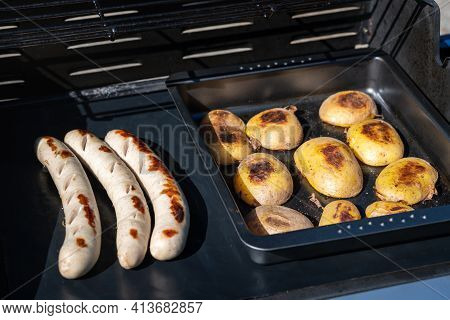 Fine Sausage With Potato Halves On The Grill. Bbq, Grill Photo, Grilling.