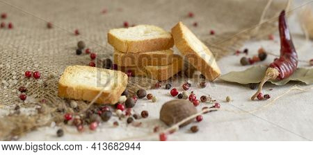 Cereal Crisps With Cereals Close-up On A Rough Linen Background With Spices, Pepper And Chili, Top V