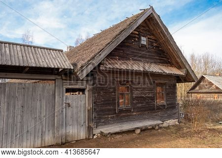 Old Wooden Peasant Hut With A Bench And A Gate