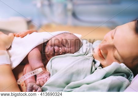 Mother And Newborn. Child Birth In Maternity Hospital. Young Mom Hugging Her Newborn Baby After Deli