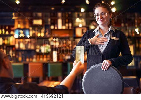 Waitress Takes The Tip. The Waiter Female Receives A Tip From The Client At The Hotel Bar. The Conce