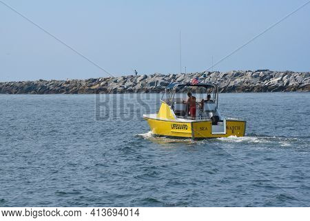 NEWPORT BEACH, CALIFORNIA - 24 AUG 2020: Lifeguard boat Sea Watch II in the Entrance Channel with the Jetty in the background.