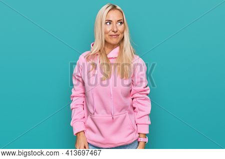 Young blonde woman wearing casual sweatshirt smiling looking to the side and staring away thinking.
