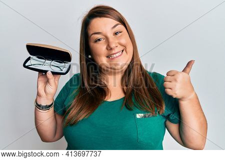 Beautiful brunette plus size woman holding glasses in eyewear case pointing thumb up to the side smiling happy with open mouth