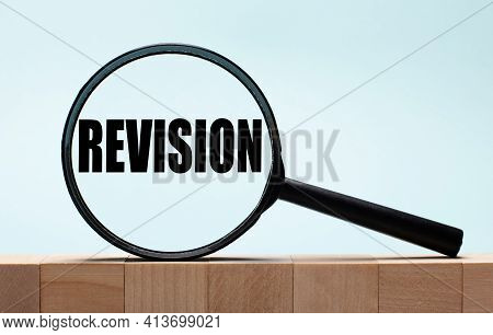 Cubes On A Light Blue Wooden Background. On Them A Magnifying Glass With The Word Revision