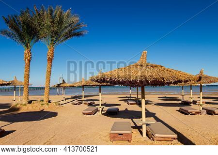 Deserted Empty Beach, Sun Loungers And Umbrellas On The Shores Of The Red Sea, Evening, Winter Sharm