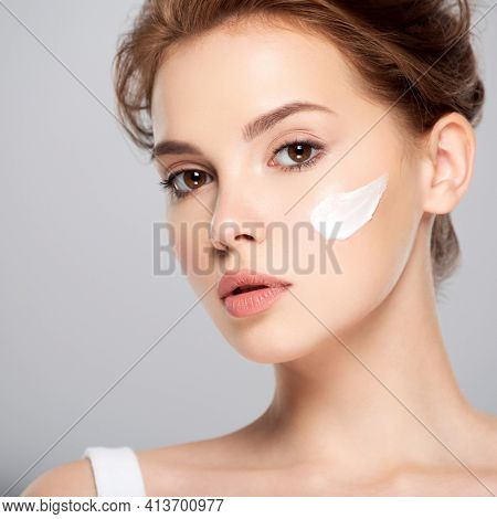 Spot of cosmetic cream on a woman's face. Beautiful face of young caucasian woman with perfect healthy skin, isolated.   Pretty white model caring of face.