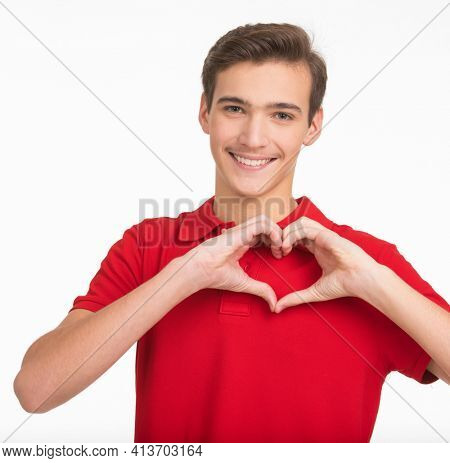 Photo of a beautiful teenager in love, isolated on white background. Young man shows gesture in the shape of a heart which means love. A gesture of love. First love