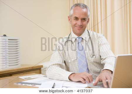 Doctor Using Laptop In Doctor'S Office Smiling