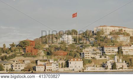 Coast With Houses And Turkish Flag. Action. Sailing Along Turkish Coast With Flag On Hill And Reside