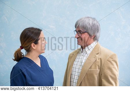 Mature Patient And Young Attractive Doctor Look At Each Other And Smile During A Conversation In A H