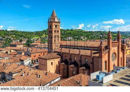 San Lorenzo Cathedral (aka Duomo) among old houses with red roofs in Old Town as green hills on background in Alba, Piedmont, Northern Italy.