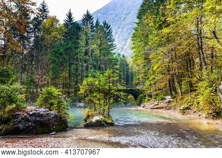 Julian Alps. Travel to Slovenia. Cloudy foggy autumn day. Picturesque shallow lake with glacial greenish water. Autumn forest and cloudy sky are reflected in the lake