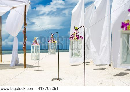 Beach Ceremony Setup With Blue Sky. Romantic Wedding Ceremony On The Beach, Candles, Flowers On Whit