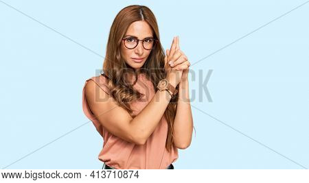 Young hispanic woman wearing casual clothes and glasses holding symbolic gun with hand gesture, playing killing shooting weapons, angry face