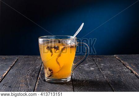 Transparent Glass Mug With Tea. Tea Leaves In A Mug. Brewing Tea In A Mug. A Teaspoon In A Mug. Fron