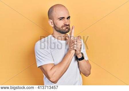 Young bald man wearing casual white t shirt holding symbolic gun with hand gesture, playing killing shooting weapons, angry face