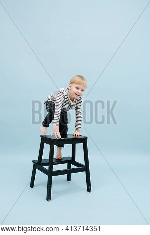 Enthusiastic Little Blond Boy Climbing On A Stepping Stool. Over Blue Background