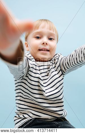 Little Blond Boy Reaching Camera With His Hands. Over Blue Background
