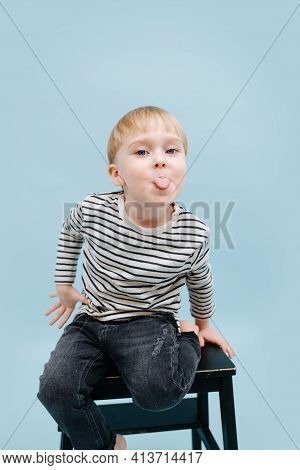 Naughty Little Blond Boy Sitting On A Stepping Stool, Stucking His Tongue Out.