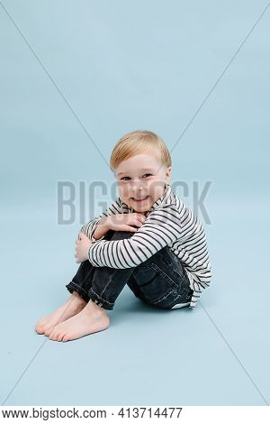Giggly Little Blond Boy Sitting On The Floor, Hugging His Knees. Over Blue