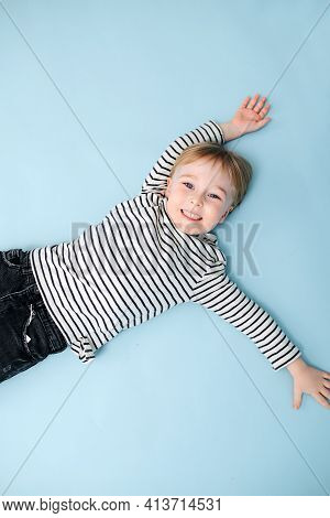 Smiling Little Blond Boy Lying On The Floor. Over Blue Background
