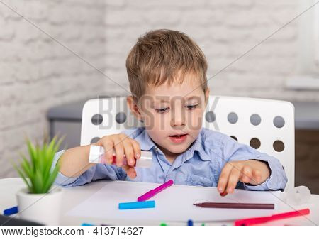 School Child Cutting Colored Paper With Scissors. Getting Creative With Cutting. Child Cutting Out S