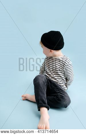 Little Blond Boy Sitting On The Floor With Legs Crossed, Looking Behind