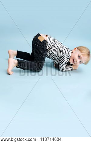 Cheerful Blond Boy Standing On All Fours, On His Knees And Elbows. Over Blue