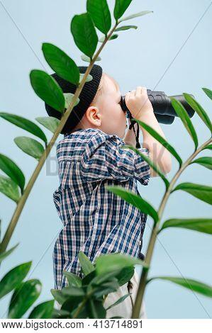 Focused Blond Boy Looking In Binoculars, Standing Behind Plant Branches